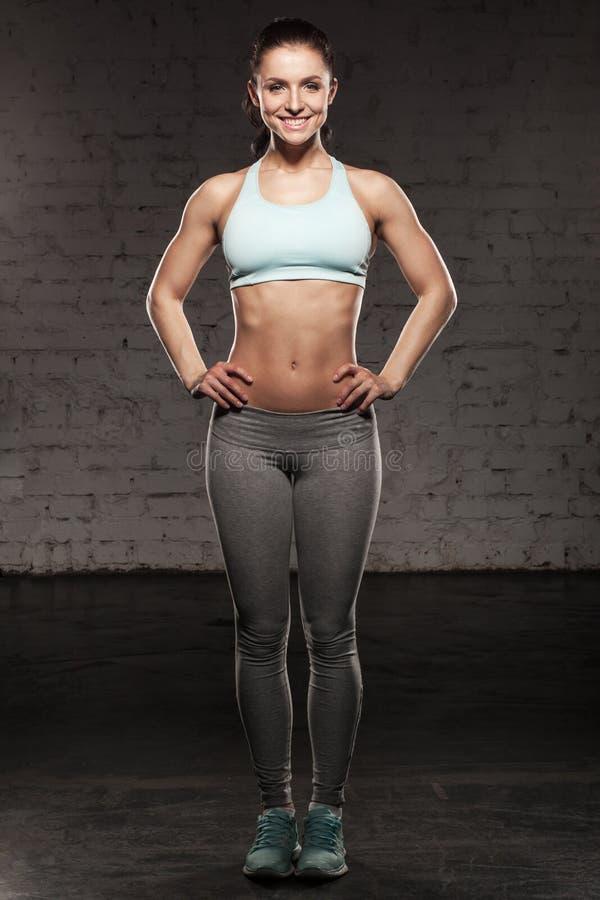 Η φίλαθλη γυναίκα με ένα όμορφο χαμόγελο, θηλυκό ικανότητας με το μυϊκό σώμα, κάνει το workout της, abdominals στοκ εικόνα