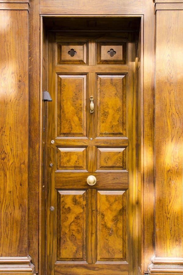 Η φανταχτερή στερεά ξύλινη μπροστινή πόρτα με τον τρύγο κοιτάζουν και η πόρτα Κ ορείχαλκου στοκ εικόνες