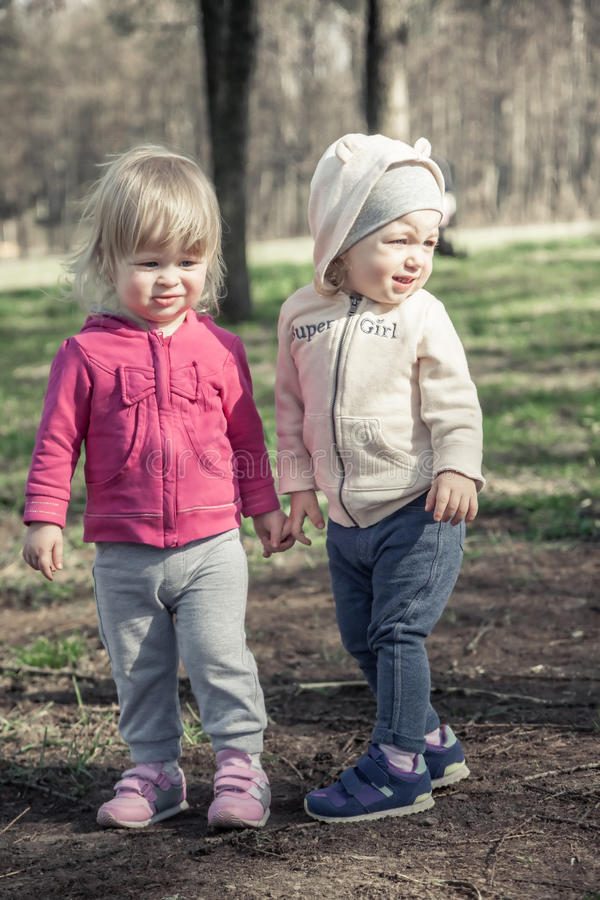 Η φιλία μεταξύ των κοριτσιών παιδιών που διατηρούν τη συνοχή με παραδίδει το θερινό πάρκο συμβολίζοντας τη φιλία και την παιδική  στοκ εικόνα με δικαίωμα ελεύθερης χρήσης