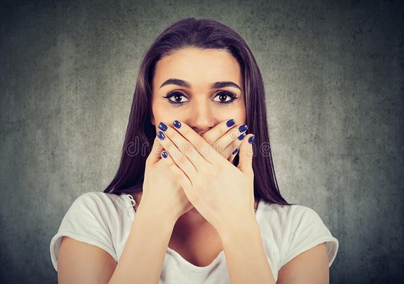 Η φοβησμένη γυναίκα καλύπτει το στόμα της για να το κρατήσει ήρεμο στοκ εικόνα με δικαίωμα ελεύθερης χρήσης