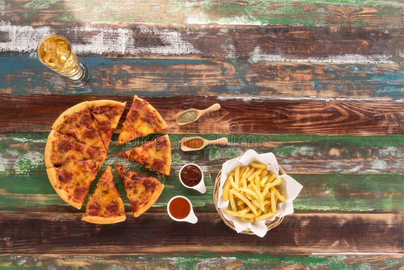 Η φρέσκες ιταλικές πίτσα και οι τηγανιτές πατάτες εξυπηρέτησαν στον αγροτικό ξύλινο πίνακα, με το ketch επάνω και το ποτό στοκ φωτογραφία