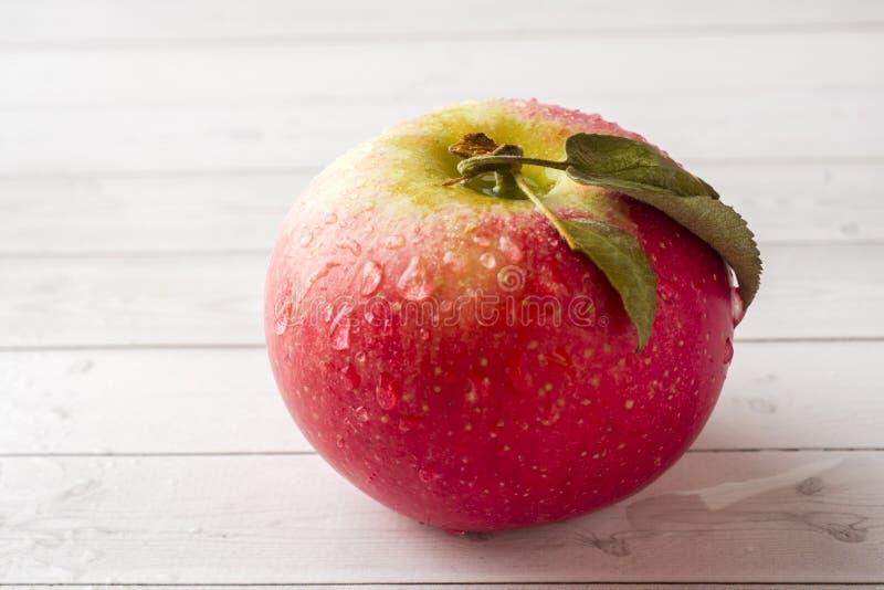 Η φρέσκια κόκκινη Apple με τα πράσινα φύλλα ελαφρύ ξύλινο στενό σε επάνω υποβάθρου Εκλεκτική εστίαση στοκ εικόνες