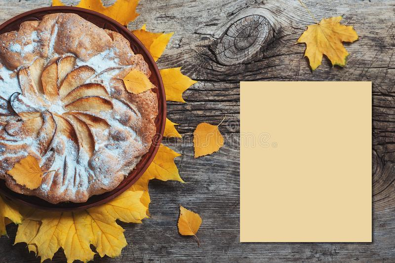 Η φρέσκια πίτα Σαρλόττα μήλων ζύμης στο ξύλινο επιτραπέζιο υπόβαθρο που διακοσμείται με το κίτρινο φθινόπωρο φεύγει Κουζίνα Cook  στοκ φωτογραφία με δικαίωμα ελεύθερης χρήσης