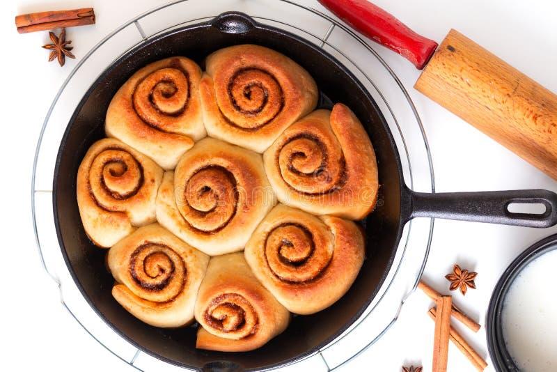 Η φρέσκια ψημένη σπιτική κανέλα έννοιας τροφίμων ψησίματος κυλά στο τηγάνι σιδήρου skillet στο άσπρο υπόβαθρο στοκ φωτογραφίες