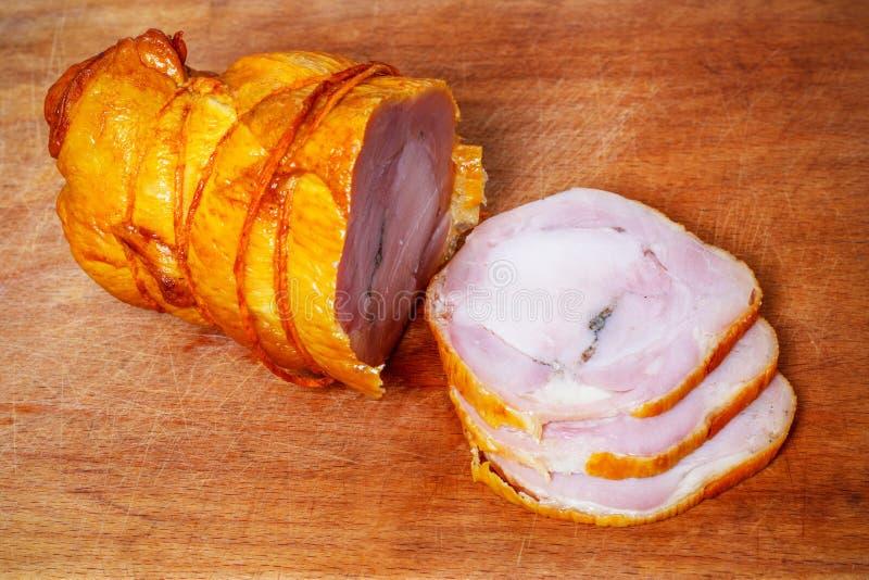 Η φραντζόλα κρέατος από το κοτόπουλο και το χοιρινό κρέας με το σκόρδο τεμάχισαν τις φέτες σε έναν ξύλινο τέμνοντα πίνακα στοκ φωτογραφία