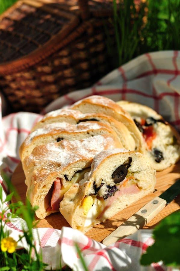 Η φραντζόλα πικ-νίκ γέμισε με το ζαμπόν, τις μαύρες ελιές, την ντομάτα, το αυγό, τα τουρσιά και το βασιλικό στοκ εικόνες