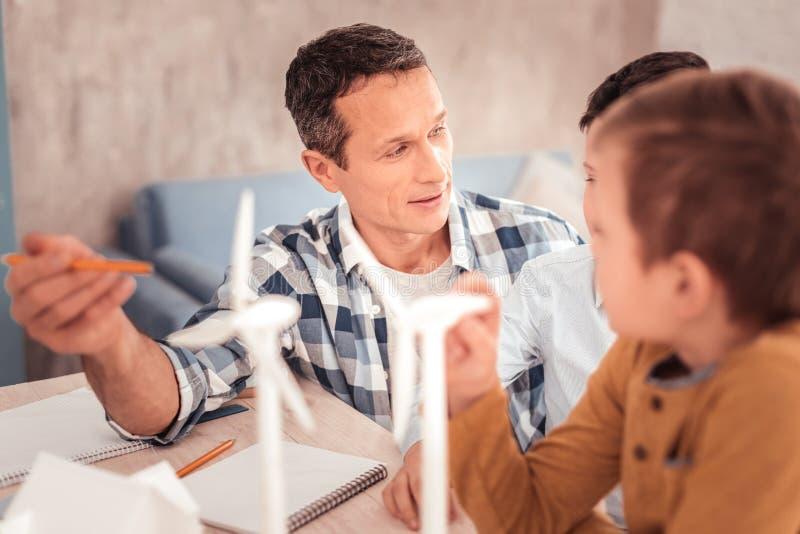 Η φροντίδα ενθαρρύνει το μολύβι εκμετάλλευσης πατέρων στο χέρι του στοκ εικόνα