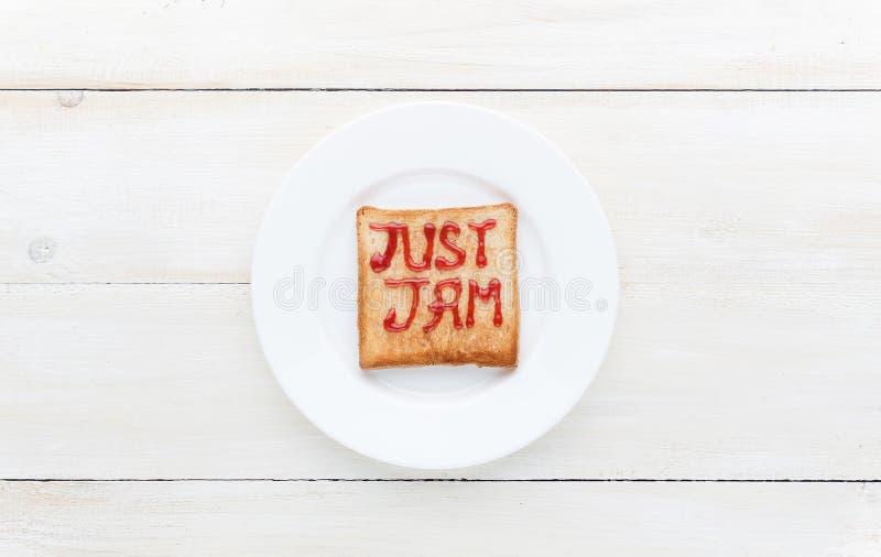 Η φρυγανιά ψωμιού με τη μαρμελάδα υπό μορφή επιγραφών το φράσσει ακριβώς στοκ εικόνες