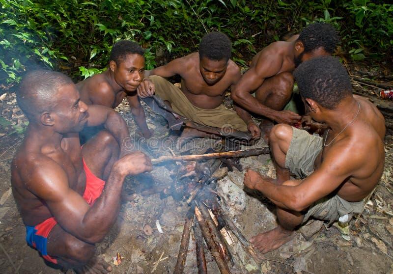 Η φυλή Yaffi ατόμων κάθεται την πυρκαγιά στη ζούγκλα στοκ εικόνες