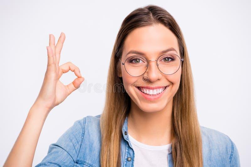Η φωτογραφία κινηματογραφήσεων σε πρώτο πλάνο εύθυμου αρκετά με τη λαμπρή ακτινοβολώντας ευθεία κυρία δοντιών που δίνει το σύμβολ στοκ εικόνα με δικαίωμα ελεύθερης χρήσης