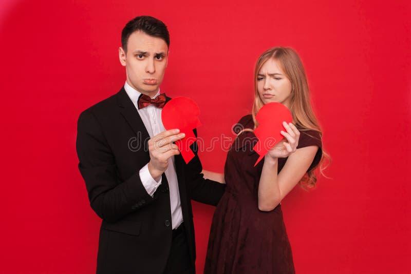 Η φωτογραφία μιας νεολαίας συνδέει, άνδρας και γυναίκα, που απομονώνονται σε ένα κόκκινο υπόβαθρο, που κρατά μια σπασμένη καρδιά στοκ φωτογραφία με δικαίωμα ελεύθερης χρήσης