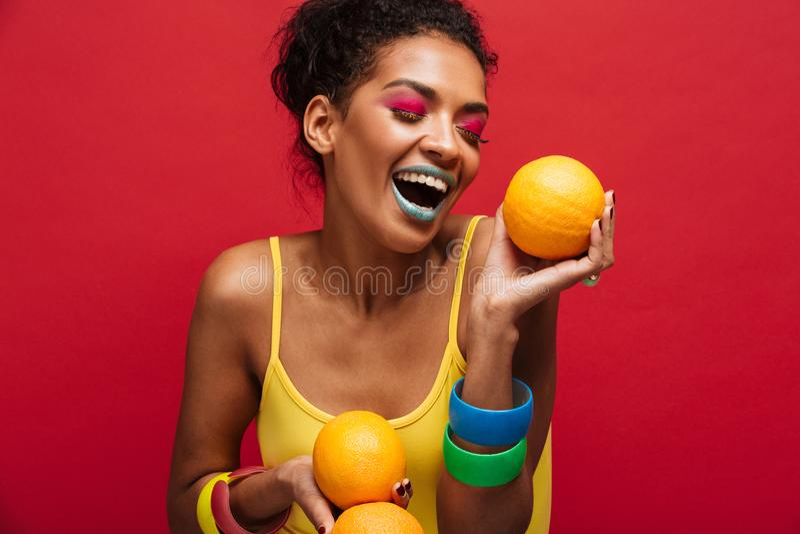 Η φωτογραφία μόδας τροφίμων της χαρούμενης γυναίκας αναμιγνύω-φυλών με ζωηρόχρωμο κάνει στοκ εικόνες με δικαίωμα ελεύθερης χρήσης