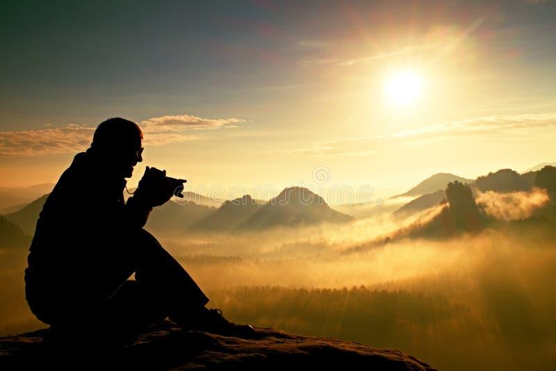 Η φωτογραφία παίρνει τις φωτογραφίες της χαραυγής επάνω από τη βαριά misty κοιλάδα Άποψη τοπίων των misty λόφων βουνών φθινοπώρου στοκ εικόνες με δικαίωμα ελεύθερης χρήσης