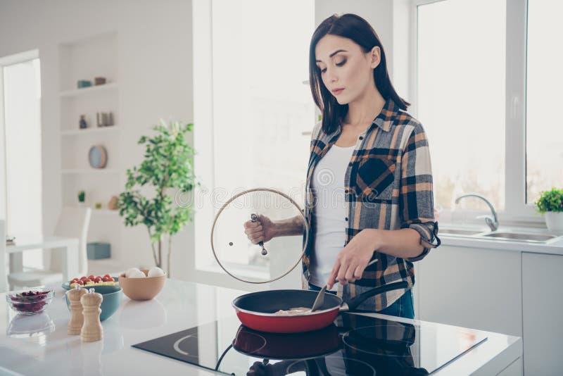 Η φωτογραφία πλάγιας όψης σχεδιαγράμματος της συγκεντρωμένης καλής γοητευτικής νοικοκυράς αρχιμαγείρων θέλει την ένδυση κουζινών  στοκ φωτογραφίες