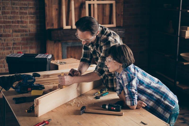 Η φωτογραφία πλάγιας όψης σχεδιαγράμματος του συμπαθητικού γοητευτικού παιδιού ξοδεύει τον οικοδόμο χρονικών μπαμπάδων χτίζει τον στοκ φωτογραφία