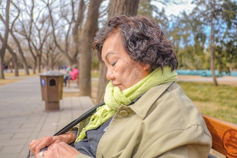 Η φωτογραφία πορτρέτου της ανώτερης ασιατικής ταξιδιωτικής συνεδρίασης γυναικών και χαλαρώνει στο ναό του πάρκου ουρανού ή Tianta στοκ εικόνα