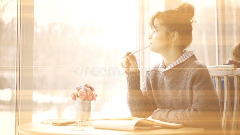 Η φωτογραφία σεπιών ενός νέου χαμογελώντας κοριτσιού brunette εξετάζει στο παράθυρο τον καφέ στοκ εικόνες με δικαίωμα ελεύθερης χρήσης