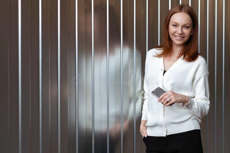 Η φωτογραφία της ευτυχούς χαμογελώντας νέας Ευρωπαίας γυναίκας που ντύνεται στα γραπτά επίσημα ενδύματα, κρατά το έξυπνο τηλέφωνο στοκ φωτογραφίες