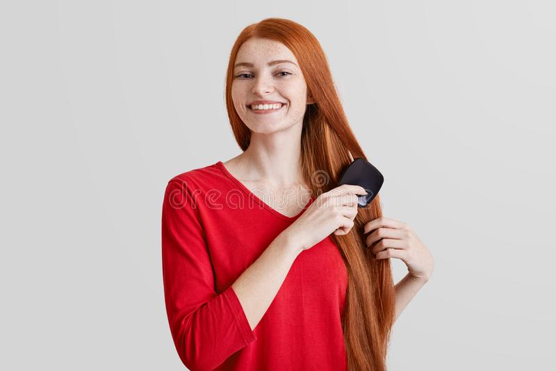 Η φωτογραφία της εύθυμης χαμογελώντας φακιδοπρόσωπης νέας γυναίκας πιπεροριζών κτενίζει τη μακριά κόκκινη τρίχα της, ευτυχή να πρ στοκ εικόνα με δικαίωμα ελεύθερης χρήσης