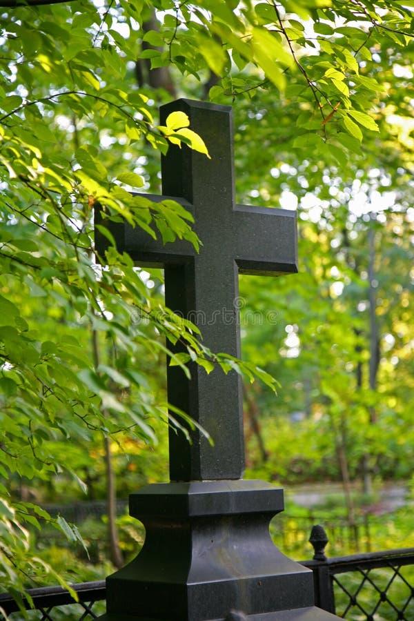 Η φωτογραφία της μαύρης πέτρας του χριστιανικού σταυρού σε ένα υπόβαθρο της ηλιοφώτιστης άφθονης πρασινάδας δασικός-πάρκων των δέ στοκ φωτογραφίες με δικαίωμα ελεύθερης χρήσης