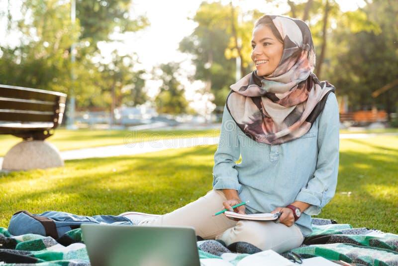 Η φωτογραφία της χαρούμενης αραβικής γυναίκας που φορά headscarf να γράψει σημειώνει κάτω στο σημειωματάριο στοκ εικόνες