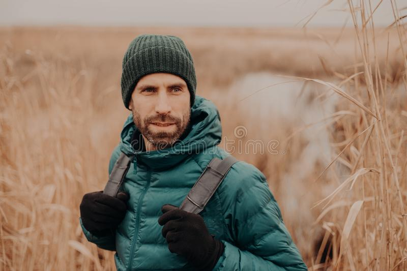 Η φωτογραφία του ελκυστικού ατόμου με τη στοχαστική έκφραση, φορά τα γάντια, καπέλο, θέτει υπαίθριο, κοιτάζει κατά μέρος, περπατά στοκ εικόνες με δικαίωμα ελεύθερης χρήσης