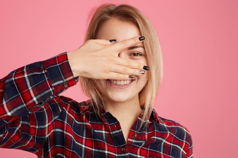 Η φωτογραφία του ευχάριστου κοιτάζοντας ξανθού ευρωπαϊκού θηλυκού κρυφοκοιτάζει μέσω των δάχτυλων, έχει το οδοντωτό χαμόγελο, εκφ στοκ εικόνα