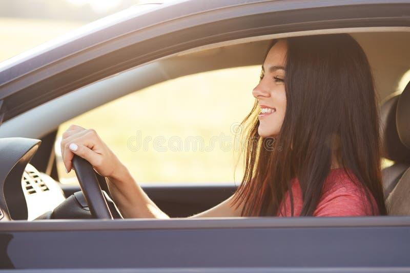 Η φωτογραφία του ευχαριστημένου ευτυχούς brunette που ο θηλυκός οδηγός εξετάζει ευτυχώς το αλεξήνεμο, κρατά τα χέρια στη ρόδα, οδ στοκ φωτογραφία