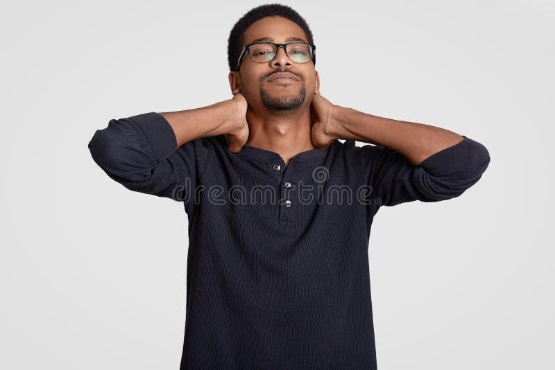 Η φωτογραφία του κουρασμένου σκοτεινού ξεφλουδισμένου νέου τύπου κρατά τα χέρια στο λαιμό, αισθάνεται τον πόνο όπως εργάζεται πολ στοκ φωτογραφία με δικαίωμα ελεύθερης χρήσης