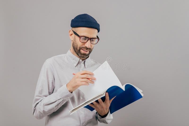 Η φωτογραφία του όμορφου αξύριστου νέου τύπου κρατά το σημειωματάριο, αναποδογυρίζει τη σελίδα, γράφει τα αρχεία και ο προγραμματ στοκ φωτογραφίες
