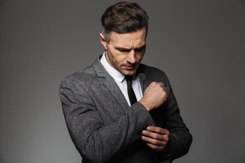 Η φωτογραφία του όμορφου μεθοδικού ατόμου που φορά το επιχειρησιακό κοστούμι στερεώνει στοκ εικόνα με δικαίωμα ελεύθερης χρήσης