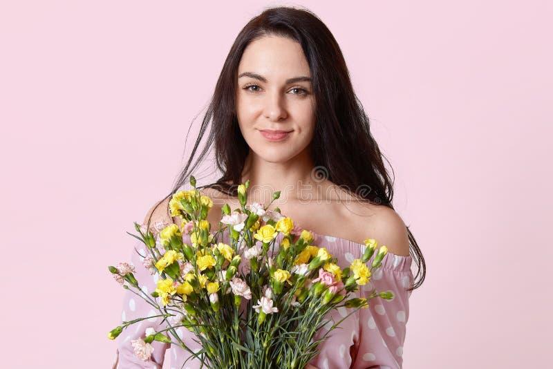 Η φωτογραφία του όμορφου brunette που η νέα γυναίκα με το ευγενές χαμόγελο, ελκυστική εμφάνιση, κρατά την όμορφη ανθοδέσμη των λο στοκ φωτογραφία με δικαίωμα ελεύθερης χρήσης