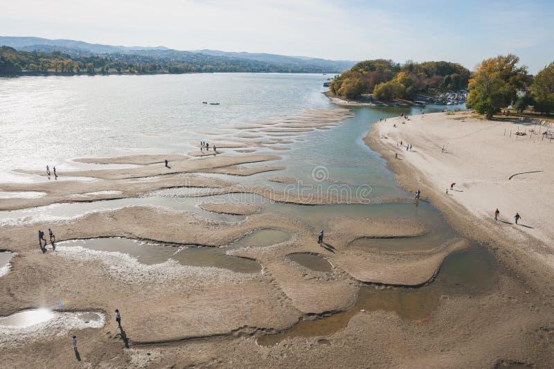 Η χαμηλή παλίρροια του ποταμού Δούναβη με τους ανθρώπους σκιαγραφεί το περπάτημα στα νησιά άμμου που αφήνονται μετά από την απόσυ στοκ φωτογραφία