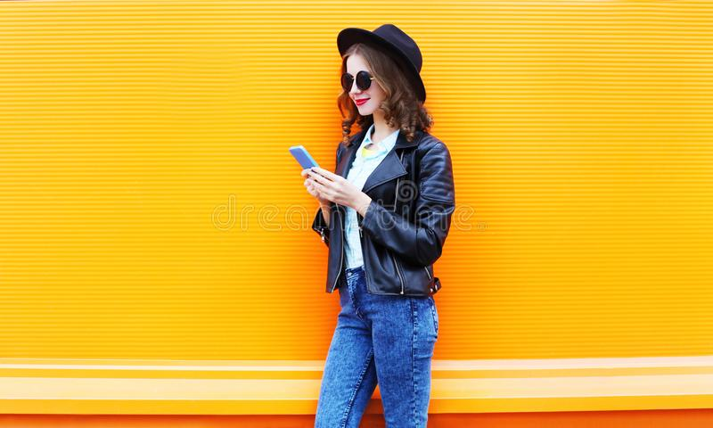 Η χαμογελώντας γυναίκα μόδας χρησιμοποιεί το smartphone στο μαύρο σακάκι βράχου στοκ εικόνα