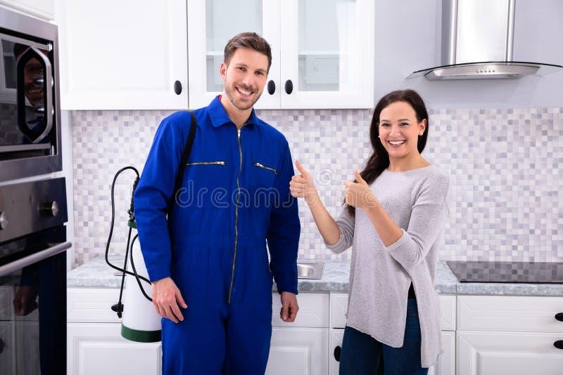 Η χαμογελώντας γυναίκα που παρουσιάζει αντίχειρες υπογράφει επάνω με τον εργαζόμενο ελέγχου παρασίτων στοκ φωτογραφία