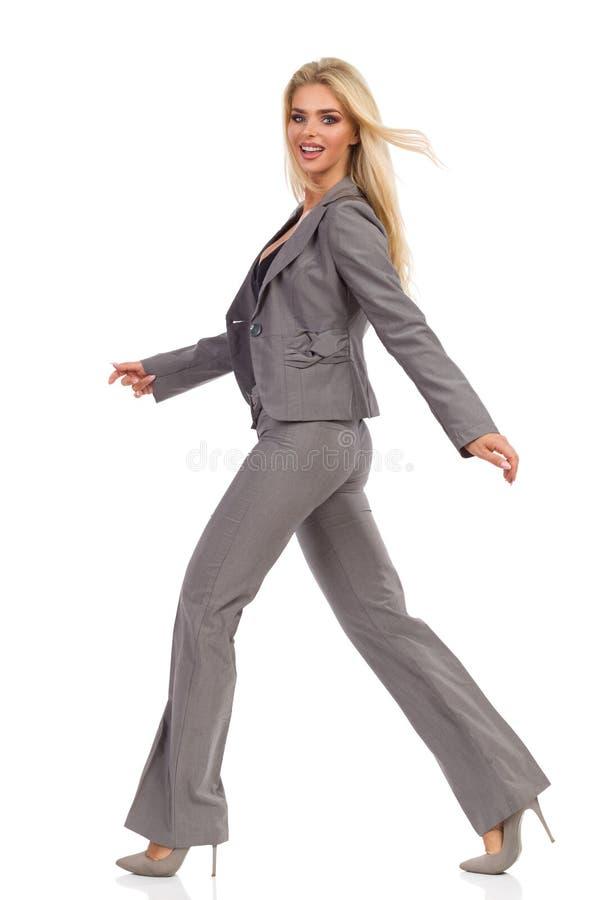 Η χαμογελώντας γυναίκα στο γκρίζο κοστούμι περπατά και εξετάζει τη κάμερα στοκ φωτογραφίες