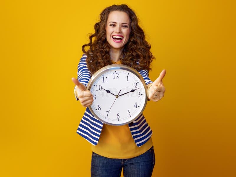 Η χαμογελώντας γυναίκα στο κίτρινο υπόβαθρο με την παρουσίαση ρολογιών φυλλομετρεί επάνω στοκ φωτογραφία με δικαίωμα ελεύθερης χρήσης