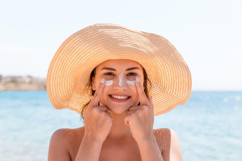 Η χαμογελώντας γυναίκα στο καπέλο εφαρμόζει sunscreen στο πρόσωπό της r στοκ εικόνες