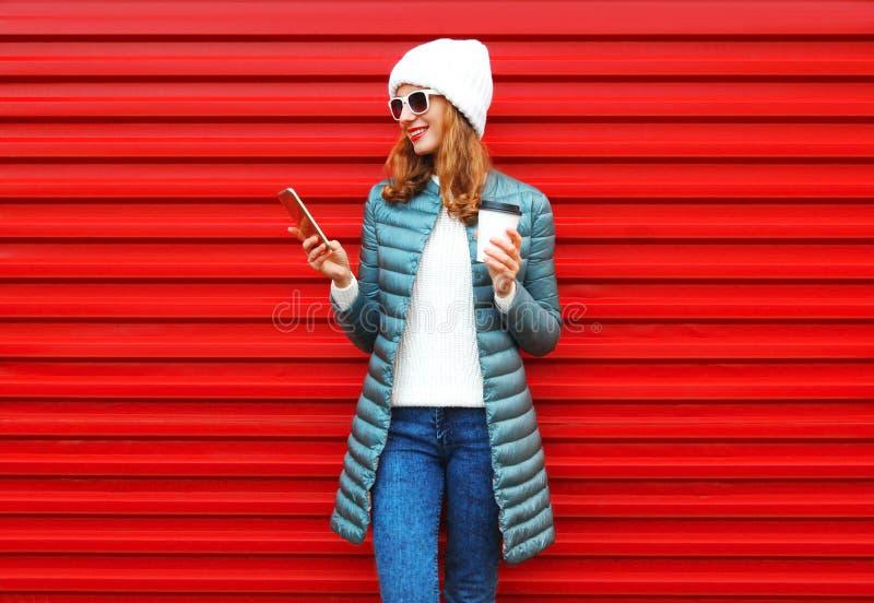 Η χαμογελώντας γυναίκα φθινοπώρου μόδας που χρησιμοποιεί το smartphone κρατά το φλυτζάνι καφέ στοκ φωτογραφία με δικαίωμα ελεύθερης χρήσης