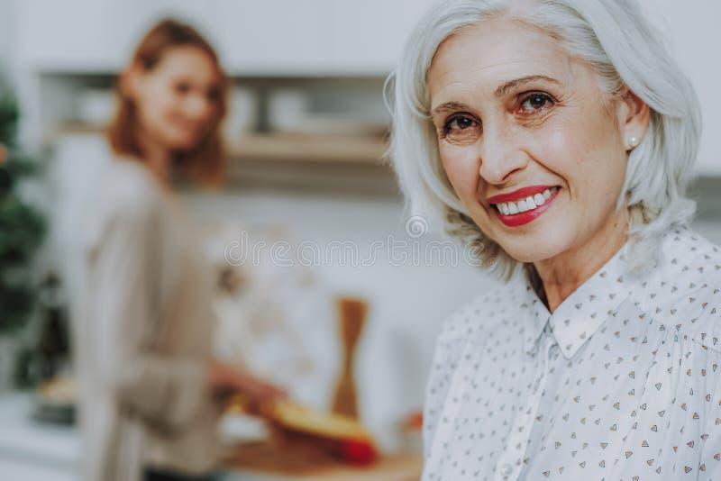 Η χαμογελώντας ηλικίας γυναίκα χαλαρώνει ενώ η κόρη της μαγειρεύει στοκ εικόνες