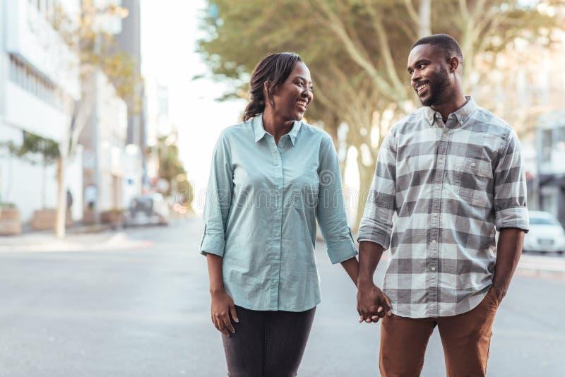 Η χαμογελώντας νέα αφρικανική εκμετάλλευση ζευγών παραδίδει την πόλη από κοινού στοκ φωτογραφία με δικαίωμα ελεύθερης χρήσης