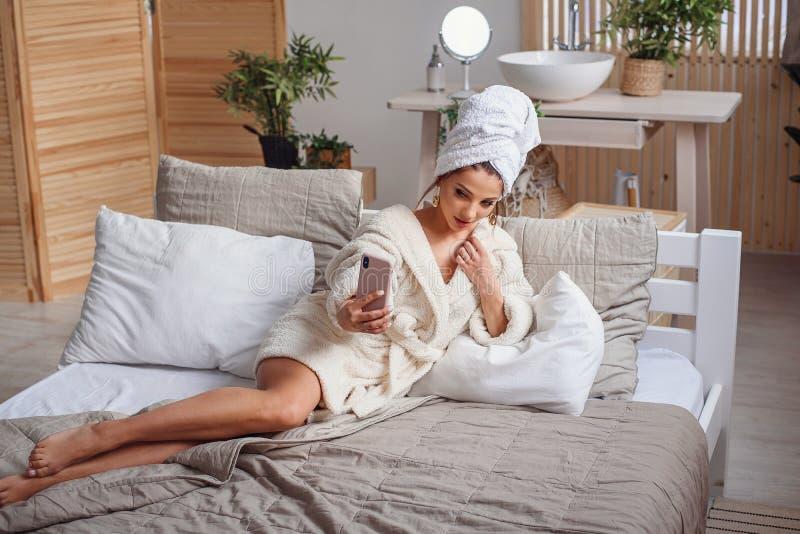 Η χαμογελώντας νέα γυναίκα βάζει στο κρεβάτι σε μια άνετη κρεβατοκάμαρα το πρωί, που ντύνεται σε ένα άσπρο μπουρνούζι και χρήσεις στοκ φωτογραφία