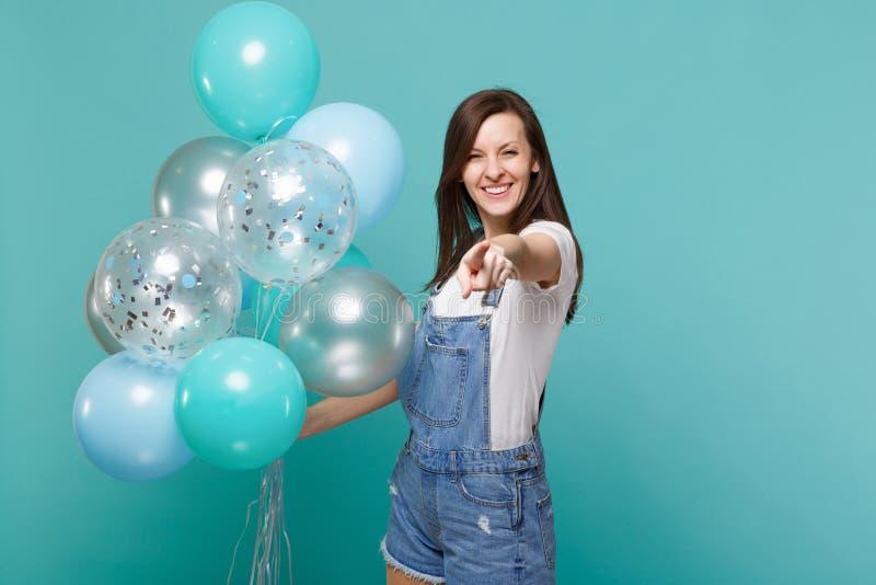 Η χαμογελώντας νέα γυναίκα στο τζιν ντύνει την υπόδειξη του αντίχειρα στη κάμερα, εορτασμός, που κρατά τα ζωηρόχρωμα μπαλόνια αέρ στοκ εικόνες