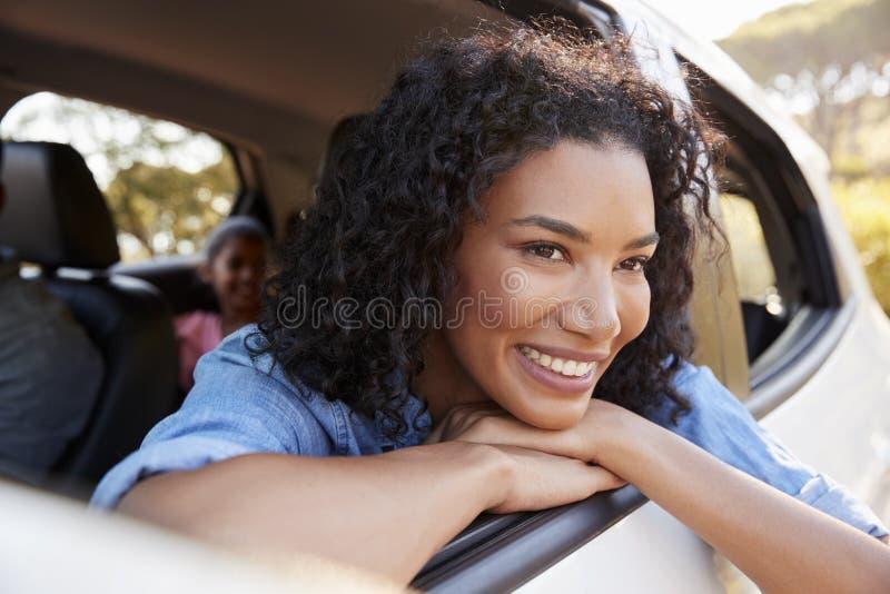 Η χαμογελώντας νέα μαύρη γυναίκα κοιτάζει από ένα παράθυρο αυτοκινήτων στοκ εικόνες με δικαίωμα ελεύθερης χρήσης