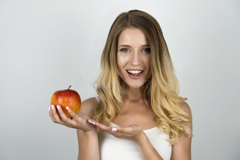 Η χαμογελώντας ξανθή ελκυστική γυναίκα που κρατά το juicy κόκκινο μήλο σε ένα χέρι απομόνωσε το άσπρο υπόβαθρο στοκ φωτογραφία