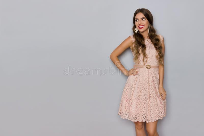 Η χαμογελώντας όμορφη γυναίκα στο μπεζ μίνι φόρεμα δαντελλών κοιτάζει μακριά στοκ εικόνες