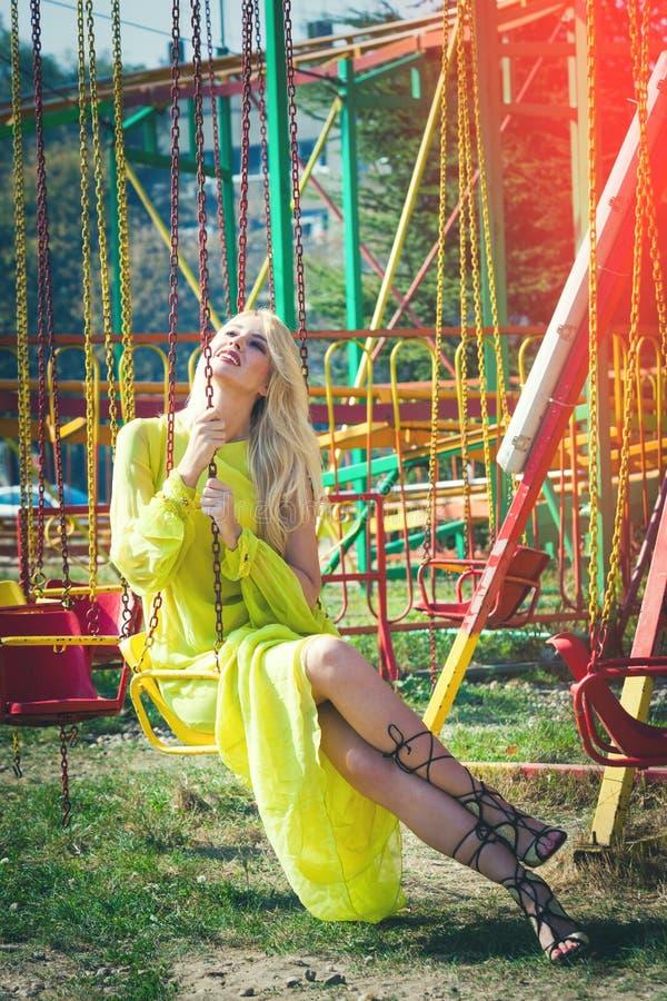 Η χαμογελώντας όμορφη ξανθή γυναίκα μόδας στο μακρύ κομψό κίτρινο φόρεμα κάθεται στο πετώντας ιπποδρόμιο το υψηλό καλοκαίρι σανδα στοκ εικόνες με δικαίωμα ελεύθερης χρήσης