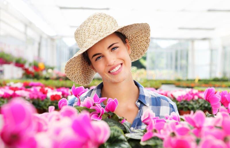 Η χαμογελώντας γυναίκα με τα λουλούδια, στο θερμοκήπιο, στοκ φωτογραφία