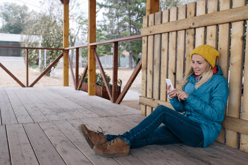 Η χαμογελώντας νέα γυναίκα κάθεται σε ένα πάτωμα του ξύλινου πεζουλιού και της χρησιμοποίησης του έξυπνου τηλεφώνου στοκ φωτογραφία