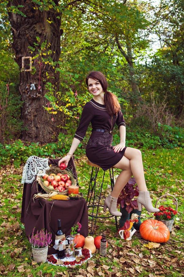 Η χαμογελώντας νέα γυναίκα με ένα μήλο παραδίδει το πάρκο φθινοπώρου στοκ εικόνες